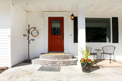 White classic porch with a red wooden door Royalty Free Stock Image