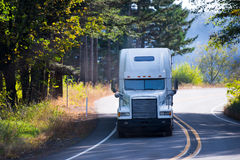 White classic semi truck big rig on winding sunny road. White classic powerful big rig long haul semi truck with a high roof transporting cargo on a bend of the stock photo