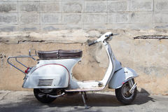 White Classic Vespa scooter stands parked near the concrete old Stock Image