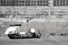 White Classic Vespa scooter stands parked near the concrete old Royalty Free Stock Photography