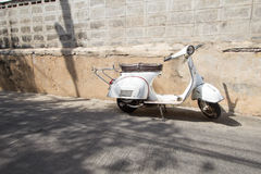 White Classic Vespa scooter stands parked near the concrete old Royalty Free Stock Photos