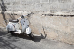 White Classic Vespa scooter stands parked near the concrete old Royalty Free Stock Image