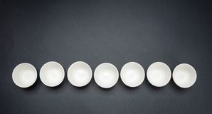 White clean ceramic bowls in a row, black background, copy space, top view. White clean ceramic bowls in a row, black color background, copy space, top view vector illustration