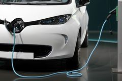 White and clean electric car charging in a garage.  royalty free stock photo