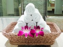 White clean hand towel in wooden basket with orchid flower Stock Photo