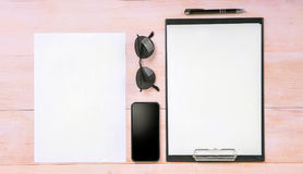 White clean sheets of paper with a thin black pen, a big black smartphone and glasses on a light brown wooden table. Stock Image