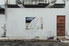 White Clean Wall with Rusted Red Wall with Ripped Poster Trace from The Street of George Town. Penang, Malaysia Royalty Free Stock Image