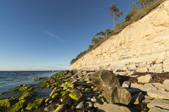 White cliff and stones at coastline Stock Photography