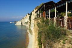 White cliffs above narrow Mediterranean beach Corfu Greece. Steep cliffs tower over Logas Beach on the Greek island of Corfu Stock Images