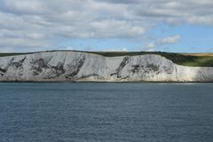 The white cliffs of Dover in England in the summer. The arrival or departure to the wonderful coastline with the white cliffs of Dover in England with the ferry stock photos