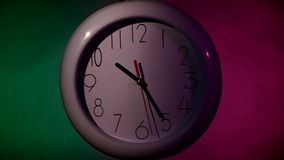 White Clock on color wooden plank wall, night. White Clock on color wooden plank wall. white office clock on colorful background. night stock footage