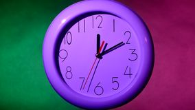 White clock on colorful background, night. Close up of an white office clock on colorful background. night, with clipping path stock video