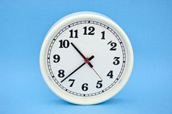 White clock dial  on blue background Royalty Free Stock Photos