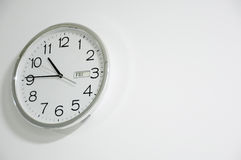 White clock hanging at the wall Stock Image
