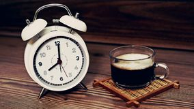 White clock 8 O`clock with coffee cup on wood background. Stock Photography