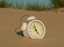 White clock on the sandy beach Stock Photo