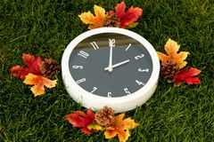 Daylight Savings Time. White clock set at 2, with grass background and fall color surrounding the clock Stock Photo