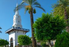 White clock tower and palm green trees in the center of Kemer, T royalty free stock photos