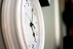 A white clock on the wall, never stops ticking Stock Image