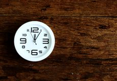 White clock on wooden wall. With space for text your. Top view Royalty Free Stock Image