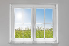 White closed window with sun. Picture of a white wall with white closed window indoor and outside green meadow with sun and blue sky Stock Image