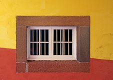White closed wooden house window in a stone frame on a brightly painted red and yellow wall in typical portuguese colors. A white closed wooden house window in a royalty free stock image