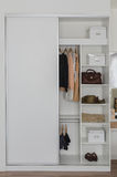 White closet with clothes and accessories. At home royalty free stock image