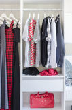White closet with shirt and dress hanging Stock Image