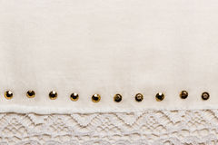 White cloth background with lace and studs. Decorative white lace cloth with metal studs background for wedding, invitation or greeting card royalty free stock image