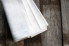 White cloth napkins. On a rustic wood surface Royalty Free Stock Photo