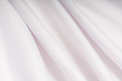 White cloth with pink shade in the folds Stock Photo