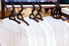 White clothes hanging on hangers in a store. For sale stock image