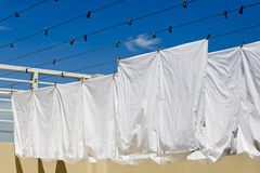 White clothes hanging on the line against blue sky. Royalty Free Stock Photos