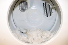 White clothes sitting in open close dryer. Very white image royalty free stock photo