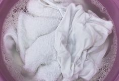 White Clothes with soap bubbles in a wash basin, top view stock photography