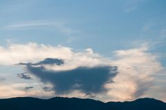 White cloud and balck cloud overlap on the sky. And silhouette mountain Stock Photography