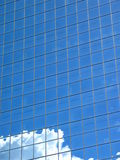 White Cloud Blue Building. Top of a fluffy white cloud reflected in the windows of a blue building stock images