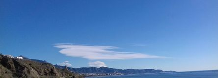 White cloud in a blue sky over mountains and sea Royalty Free Stock Images