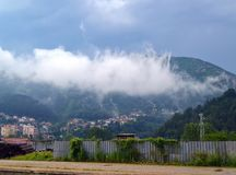 A white cloud descended on the village at the foot of a forested mountain. Landscape: a white cloud descended on the village at the foot of a forested mountain Stock Photos