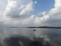 White cloud reflection on water with two boats at distance. Mukutmanipur dam water to the horizon , reflection of white cloud and blue sky and two boats at Stock Image