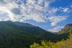White clouds above blue mountains Royalty Free Stock Image
