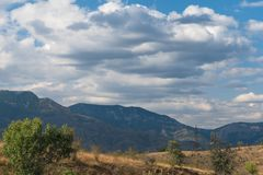 White clouds above blue mountains Stock Photography