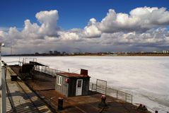 White clouds above the frozen river. The river Аmur in the spring Stock Image