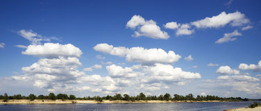 White clouds above the river . Stock Images