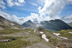 White clouds above water reservoir in the Alps Royalty Free Stock Photos