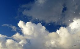 White clouds against deep blue skies, raindrops on window. stock photography