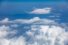 White clouds background hanging on blue sky over mountain. Aerial photo from airplane`s window. Royalty Free Stock Image