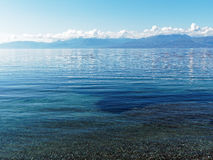 White Clouds and Blue Mountains Reflected in Ocean Royalty Free Stock Photo