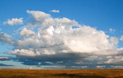 White clouds and blue sky. Of a storm approaching over grass fields Stock Photo