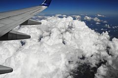 White clouds and blue sky from airplane window Stock Photo